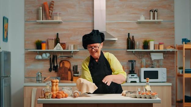 Frau mit knochen hat spaß beim kochen zu hause in der modernen küche und macht staub mit mehl. geschickter pensionierter älterer koch in uniform, der sich dreht und pizzateig wirft, um ihn hochzuwerfen