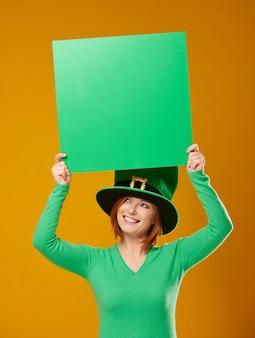 Frau mit koboldhut zeigt grünes banner