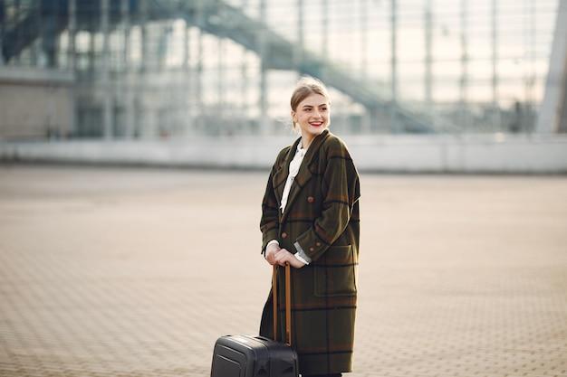 Frau mit koffer, der durch den flughafen steht