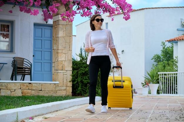 Frau mit koffer, die im freien durch das gebiet des malerischen kurorthotels des meeres mit schöner rosa blumenlandschaft geht reisen, urlaub, freizeit, wochenende, leute