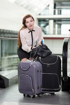 Frau mit koffer und flugtickets am flughafen.