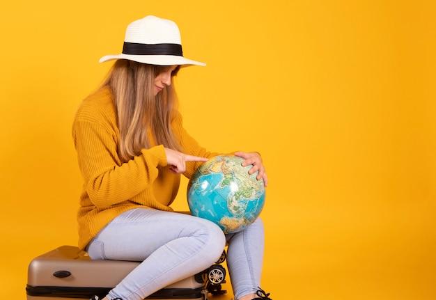 Frau mit koffer und hut schaut auf erdkugel will reisen