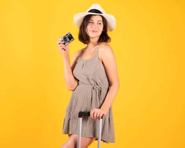 Frau mit kofferhut und fotokamera-reisender, tourist. auf gelbem hintergrund