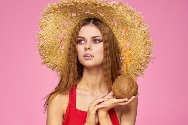 Frau mit kokosnusscocktail im strohhut exotischen urlaubsrosa rosa wand.