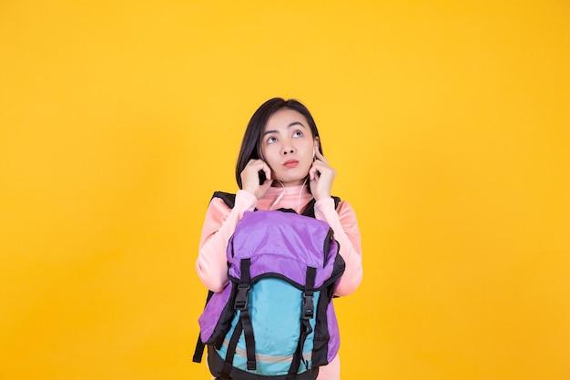 Frau mit kopfhörer zum musikhören auf gelbem hintergrund