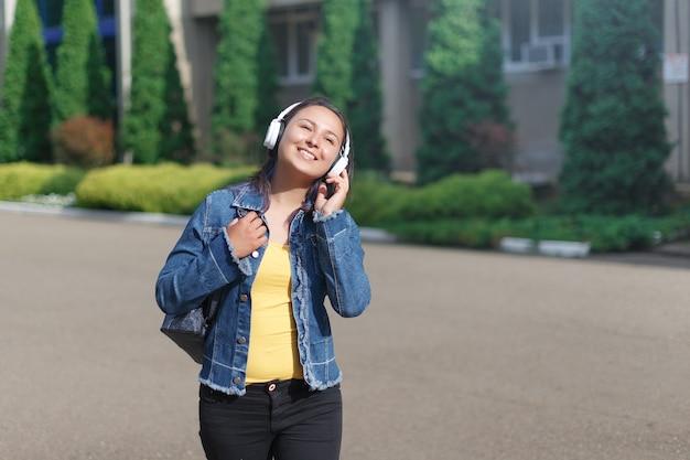 Frau mit kopfhörern, die an einem sonnigen tag im park spazieren geht und musik hört