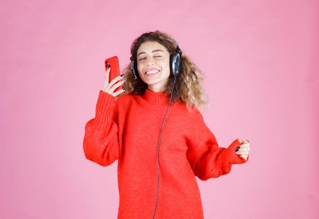 Frau mit kopfhörern, die ihre playlist auf dem smartphone hört und tanzt.