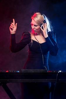 Frau mit kopfhörern, die musik mischen