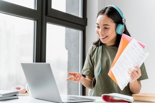 Frau mit kopfhörern, die videoanruf auf laptop haben