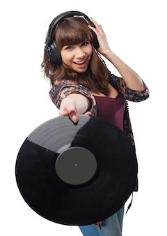 Frau mit kopfhörern eine vinyl-schallplatte zeigt