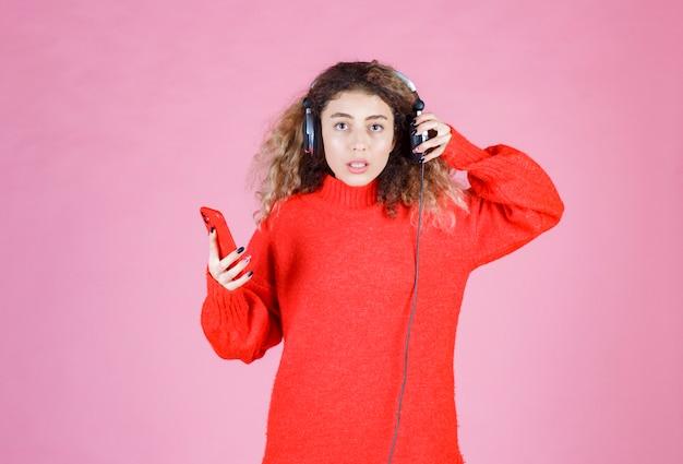 Frau mit kopfhörern hört ihre playlist auf dem smartphone und sieht unzufrieden aus.