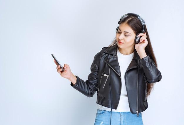 Frau mit kopfhörern hört und genießt die musik.