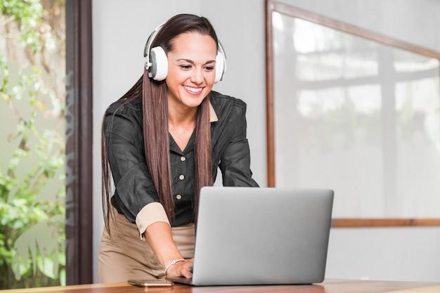 Frau mit kopfhörern ihren laptop überprüfend