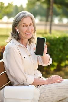 Frau mit kopfhörern mit smartphone-bildschirm