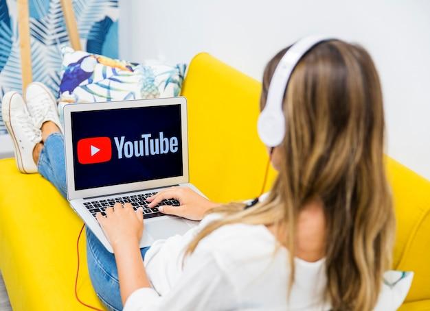 Frau mit kopfhörern und laptop auf beinen