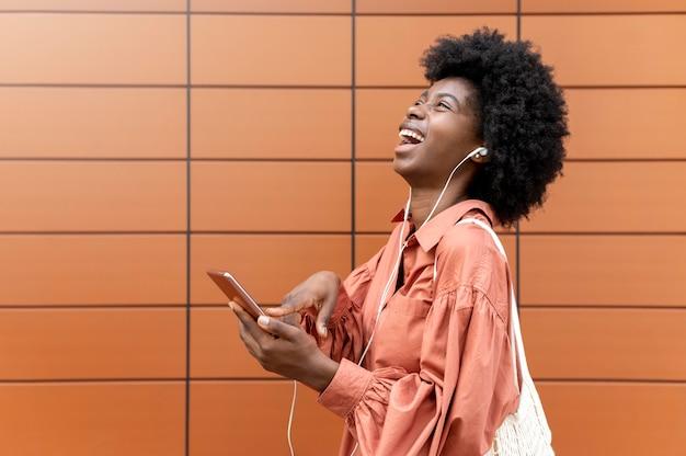 Frau mit kopfhörern, während sie ihr smartphone hält