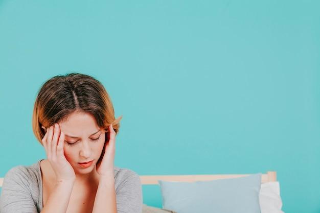 Frau mit kopfschmerzen auf dem bett