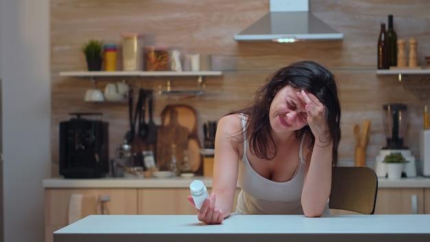 Frau mit kopfschmerzen, die pillenflasche hält, die die informationen liest. gestresste, müde, unglückliche, besorgte person, die an migräne, depressionen, krankheiten und angstzuständen leidet, sich mit schwindelsymptomen erschöpft fühlen
