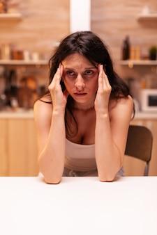 Frau mit kopfschmerzen. gestresste, müde, unglückliche, besorgte person, die an migräne, depressionen, krankheiten und angstzuständen leidet, sich mit schwindelsymptomen erschöpft fühlen
