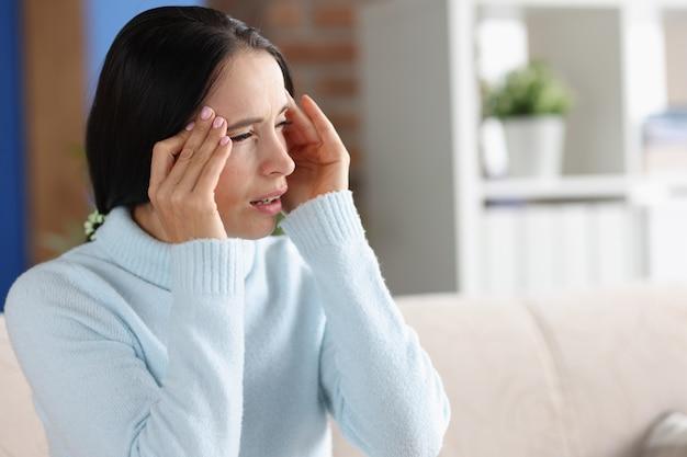 Frau mit kopfschmerzen und photophobie schaut aus dem fenster. hauptgründe für das photophobie-konzept