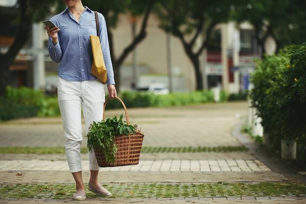Frau mit korb des neuen lebensmittels und des smartphone, die draußen stehen