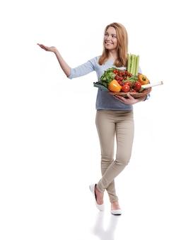 Frau mit korb voller gesunder nahrung, die auf kopienraum zeigt