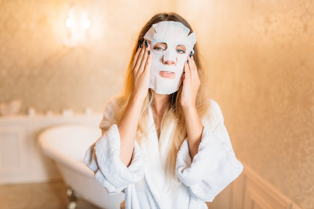 Frau mit kosmetischer gesichtsmaske, hautpflege im badezimmer. körperpflege und hygiene, gesundheitswesen, schönheitsprodukte