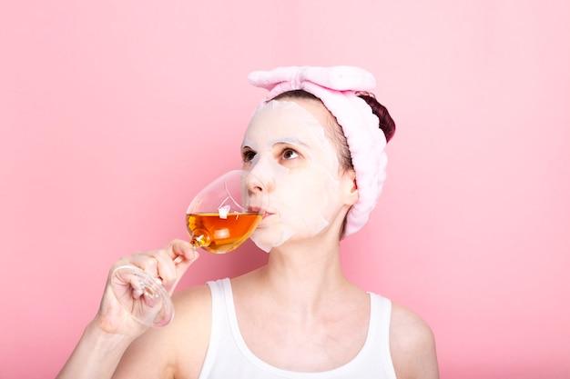 Frau mit kosmetischer maske auf ihrem gesicht hält glas weißwein auf rosa raum. konzept spa tag zu hause, ruhe und entspannung