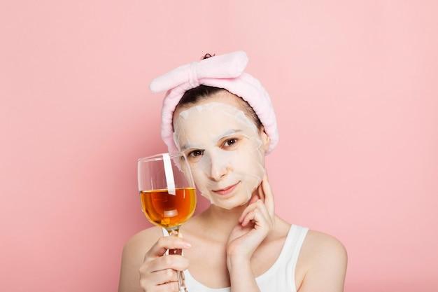 Frau mit kosmetischer maske auf ihrem gesicht hält glas weißwein, lächelt und berührt handgesicht auf rosa raum. konzept spa tag zu hause, ruhe und entspannung