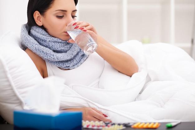 Frau mit kranken erkältungen des thermometers, grippe, fieber, kopfschmerzen im bett