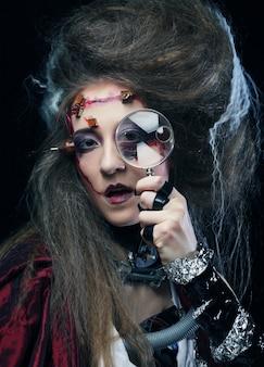 Frau mit kreativem make-up, das eine lupe hält