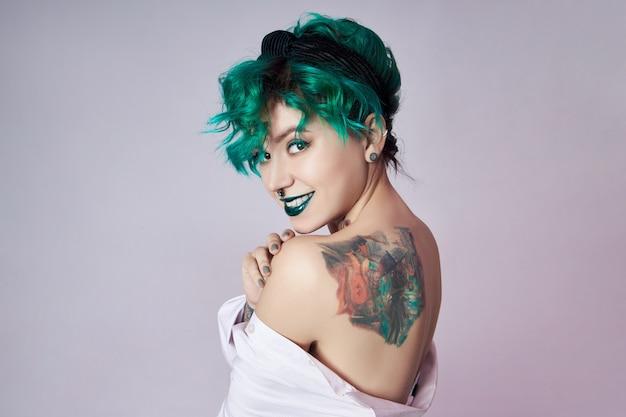 Frau mit kreativen grünen haaren und make-up, giftige haarsträhnen. helles lockiges haar auf dem mädchenkopf, professionelles make-up. frau mit tätowierung