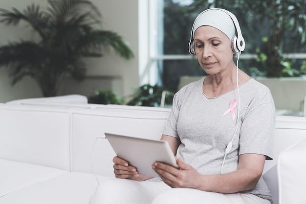 Frau mit krebs sitzt auf sofa in einer modernen klinik.