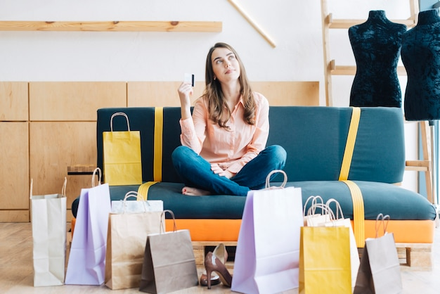 Frau mit kreditkarte auf sofa