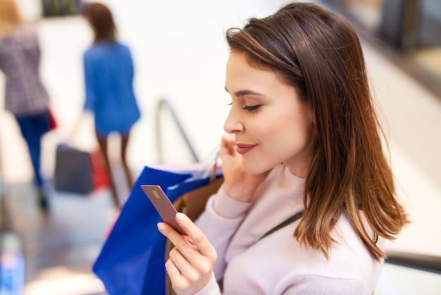 Frau mit kreditkarte beim großen einkaufen