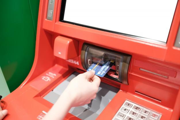 Frau mit kreditkarte, um geld von atm machine abzuheben.