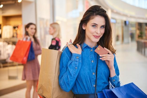 Frau mit kreditkarte und vollen einkaufstüten