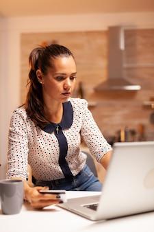 Frau mit kreditkarte während der online-transaktion mit laptop in der heimischen küche spät in der nacht. kreative dame, die online-zahlung mit digitalem notizbuch macht, das mit dem internet verbunden ist