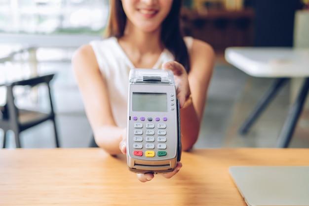 Frau mit kreditkarten-wischmaschine