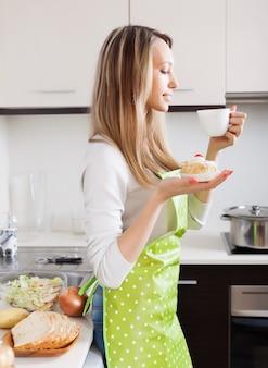 Frau mit kuchen und tee in der küche