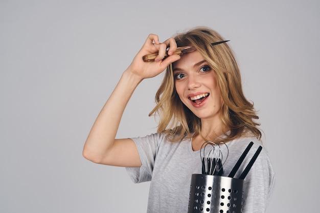 Frau mit küchengeräten auf grauem hintergrund emotionen modell hausfrau