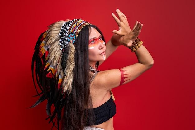 Frau mit kunst indianischem kreativem kriegerkampf-make-up im studio, rituale machend. indische jägerin in traditioneller ethnischer tracht mit federn
