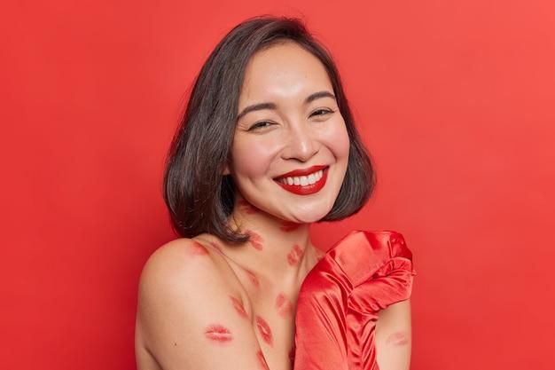 Frau mit kurzen dunklen haaren lächelt zahnig hält die hände zusammen sieht sanft aus trägt lange handschuhe hat lippenspuren am körper auf leuchtendem rot