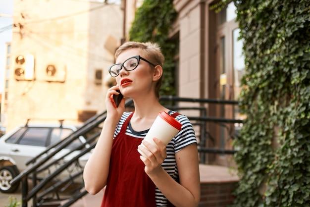 Frau mit kurzen haaren, die eine brille auf der straße trägt und am telefon telefoniert
