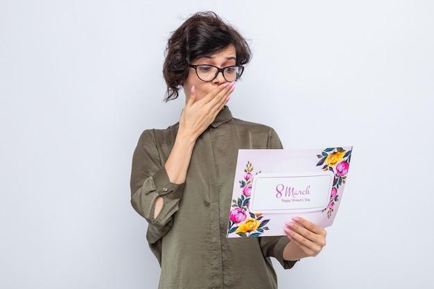 Frau mit kurzen haaren, die eine grußkarte hält und sie erstaunt betrachtet, die den mund mit der hand bedeckt, die den internationalen frauentag am 8. märz feiert