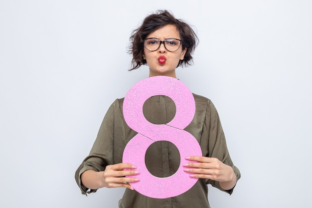 Frau mit kurzen haaren, die nummer acht aus pappe hält, die verwirrt aussieht und die lippen hält, als würde sie den internationalen frauentag am 8. märz küssen