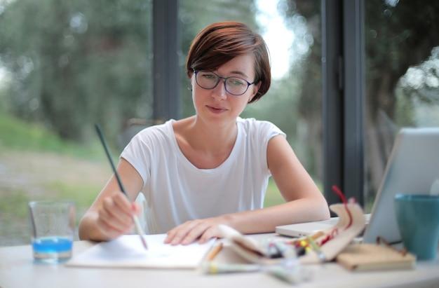 Frau mit kurzen haaren, die versuchen, mit einem pinsel in ihren händen zu zeichnen