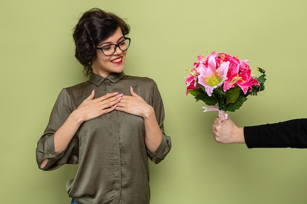 Frau mit kurzen haaren, die zufrieden und glücklich aussieht, während sie einen blumenstrauß von ihrem freund erhält, der den internationalen frauentag am 8. märz über grünem hintergrund feiert