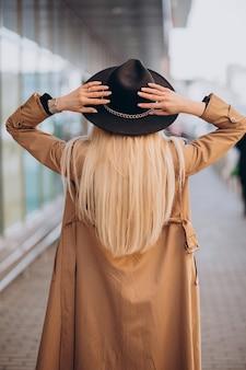 Frau mit langen blonden haaren, die mit ihrem rücken stehen