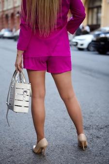 Frau mit langen blonden haaren im rosa anzug mit tasche in der handansicht von hinten geht.